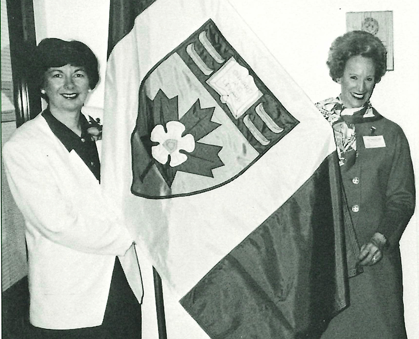 Nora (Mitchell) Newlands '67 and Pauline (Agnew) Hall '54 holding the new YHS Flag on April 28, 1993, after the proclamation of the YHS Coat of Arms and Heraldic Flag as part of the school's 60th Anniversary